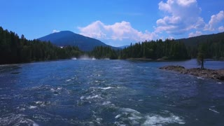 Aerial Drone Traveling Low Along Flowing Water With Mountains In Background 2