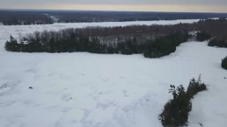 Aerial Drone View Flying Over Frozen Ice Lake Following Snowmobile Rider In Winter 1