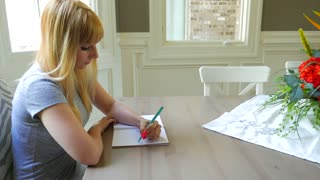 Attractive Female Writing In Her Journal Book In Dining Room 02