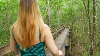 Blonde Female In Dress Walking On Path Through Florida Slough Marsh 01