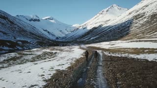 Iceland Aerial View Of Two People Hiking Along Path Towards Large Snow Covered Mountains 1