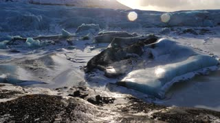 Iceland Giant Blue Glacier Ice Chunks With The Sun Peaking 3