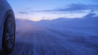 Iceland Low View Of 4 X 4 Vehicle Driving As Strong Winds Blow Snow Over Highway 1