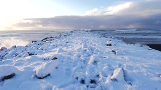 Iceland Moving Along Snow Covered Pier With Crashing Ocean Waves 1