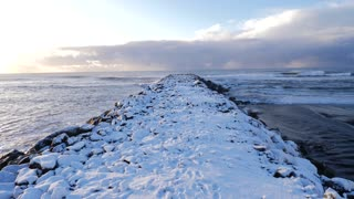 Iceland Moving Along Snow Covered Pier With Crashing Ocean Waves 2