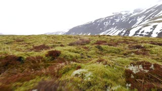 Iceland Moving Fast Over Green Moss Covered Ground With Mountains In Winter 1