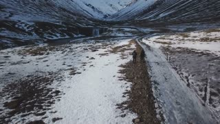 Iceland Winter Aerial View Of Two People Hiking Along Path Towards A Large Mountain Mountain 1