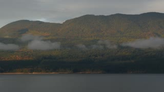Pan Of Beautiful British Columbia Lake With Mountains And Low Clouds 02