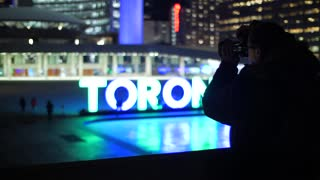 Photographer At Night Taking Picture Of Toronto Sign At City Hall 1