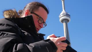 Photographer Reviewing Photos With Cn Tower In Background 1