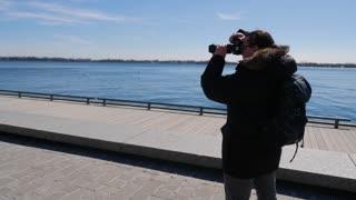 Photographer Walking Along Waterfront Boardwalk Taking Photos 1