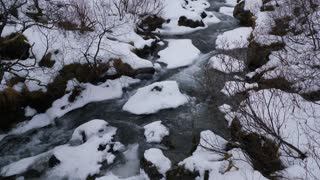 Snow Covered Valley With Rushing Water In Iceland During Winter 1
