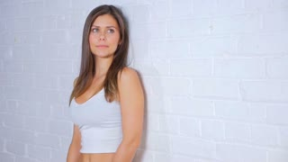 Young Attractive Female Doing Different Poses While Smiling And Leaning Against A White Brick Wall 2