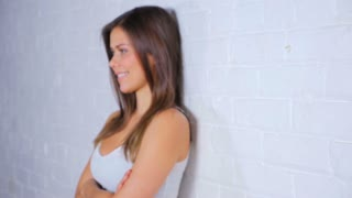 Young Attractive Female Turning To Camera And Smiling While Leaning Against A White Brick Wall 2
