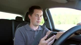 A man siting in the car and speaking on mobile phone