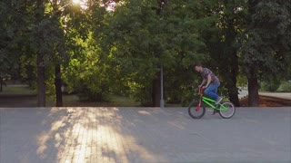 A young boy fulfills tricks in the BMX park by bicycle.