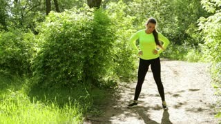 Active young sport woman doing fitness exercises in the park near a forest