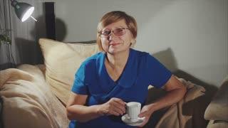 An elderly senior woman drinking coffee sitting on the chair