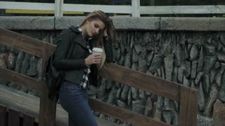 Attractive blonde young woman drinking coffee outdoor