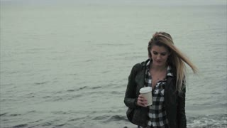 Attractive young blond woman holding a cup of coffee in her hands near the sea