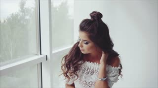 Attractive young woman brunette posing sitting near the window
