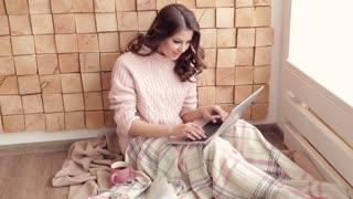 Beautiful girl using laptop and smiling at camera