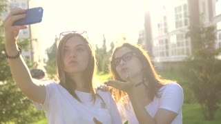 beautiful girls friends taking selfies in the city sunset strong back light