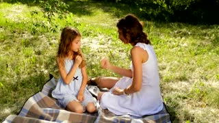 Beautiful mom and daughter playing a game of rock, paper, scissors in the park