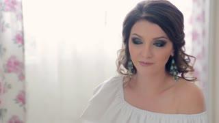Beautiful woman makeup looking at the mirror