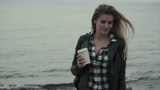 Beautiful young blond woman holding a cup of coffee in her hands near the sea