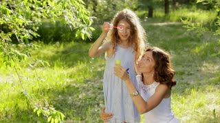 Beautiful young mother together with her daughter in nature making soap bubbles