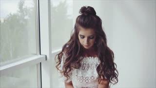 Beautiful young woman brunette posing sitting near the window