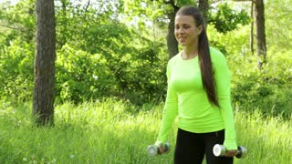 Beautiful young woman doing exercise whith dumbbell forest summer day