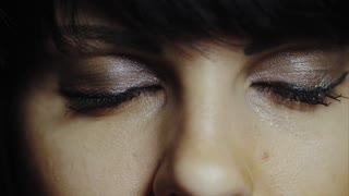 Brunette opening her green eyes in extreme close up