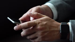 Business man using smartphone typing text wearing smart watches on his hand