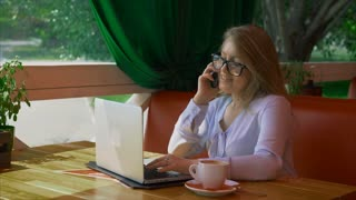 Business woman wearing glasses working in cafe and talking on smart phone