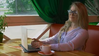 Businesswoman wearing glasses working in cafe and talking by video communication