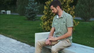 Casual dressed man sit on the bench in the park and use his modern smart watch