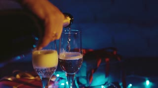 Champagne pouring from the bottle, two flutes with sparkling wine bokeh blinking