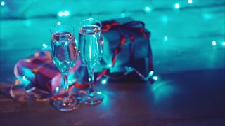 Close up christmas presents and two glasses of bubbling champagne blue bokeh