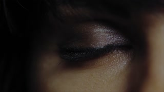 Close up macro shot of young woman's green eye with make up open