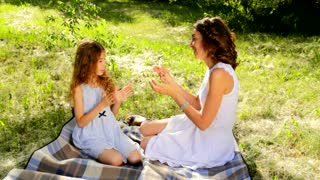 Close up of attractive young mom and her cute daughter playing clapping game