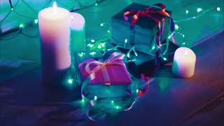 Close up of christmas and new year gift boxes and candles with blue garland