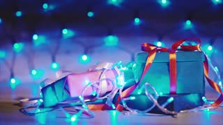 Close up of christmas and new year gift boxes with blue flashing garland