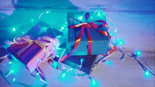 Close up of christmas and new year presents with blue flashing garland