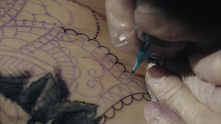 Close-up of hands of tattoo artist in gloves tattooing a pattern on body macro