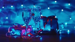 Close up of xmas and new year presents, two glasses champagne with blue garland