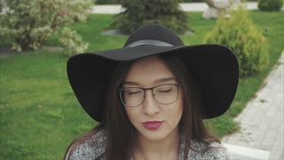 Close up portrait of pretty smiling woman in black hat and glasses in the park
