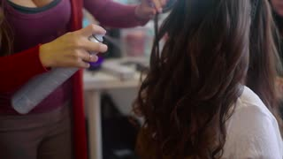 Close up shot of hairdresser sprays hairspray on brunette while making hair-do