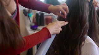 Close up shot of hairdresser sprays hairspray on brunette while making hair-do